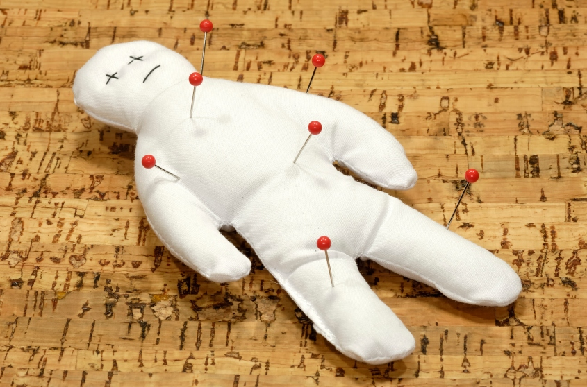 A white voodoo doll with five red pins in it