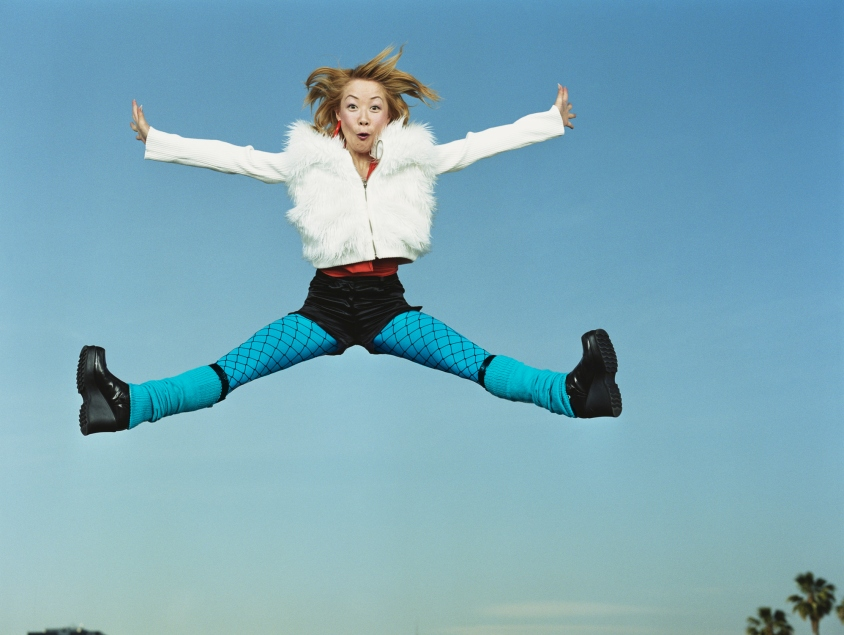 Young woman jumping in air, arms and legs outreached, portrait