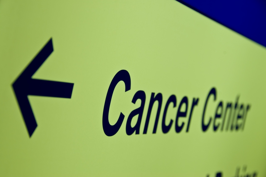 Close-up of a sign and arrow leading to the cancer center
