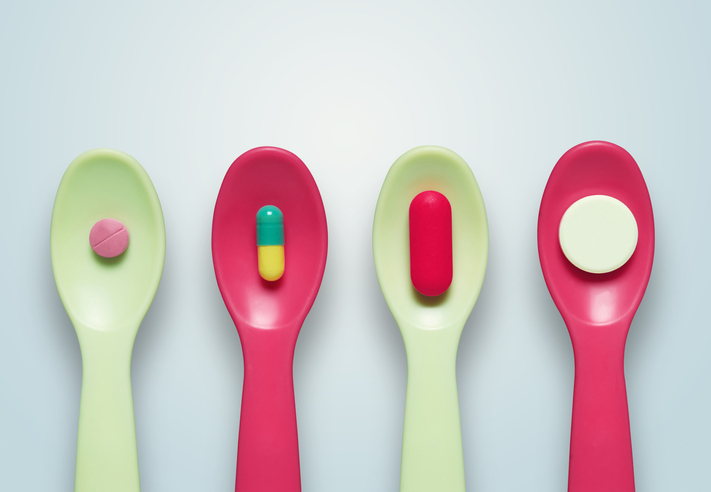Four plastic spoons each containing a different pill