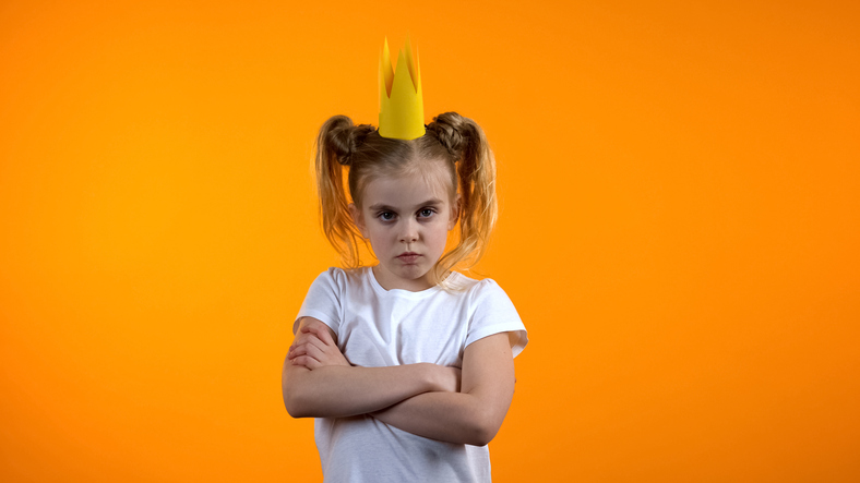 Funny naughty child in princess crown standing with hands crossed on chest