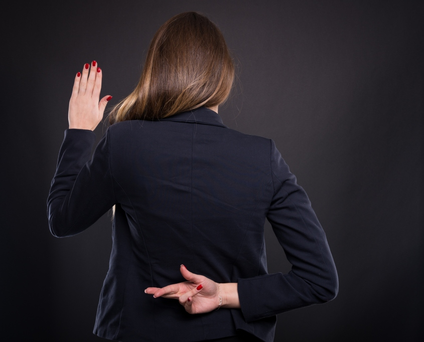Businesswoman with crossed fingers behind her back